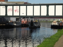 Boaters in Hackney Wick passing under a bridge which the freights rattle across at night.